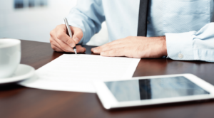 Man signing PR contract with ipad in front
